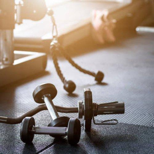 Gym background Fitness weight equipment on empty dark floor